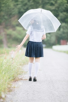 Portrait of asian school girl walking with umbrella at  nature walkway on raining