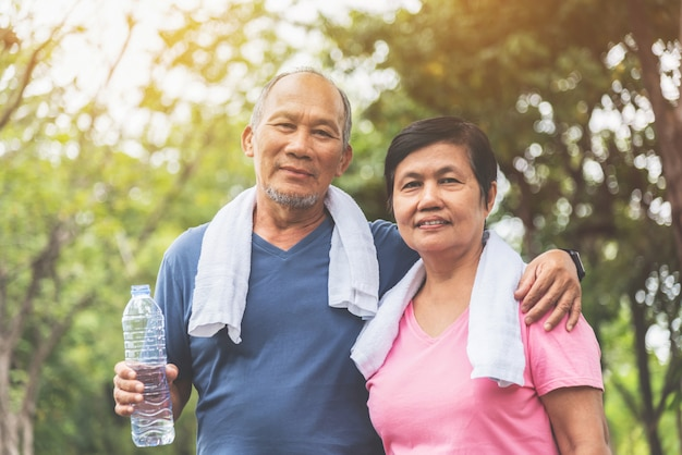 Portrait of asian senior couple in blue and pink shirt smiling and standing at park outdoor.
