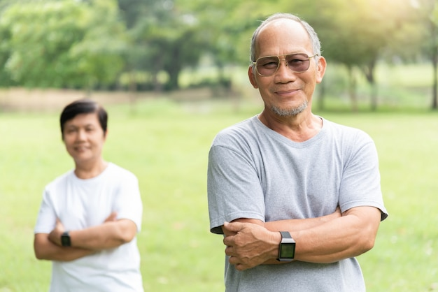Portrait of asian senior couple smiling with arms crossed before exercising.