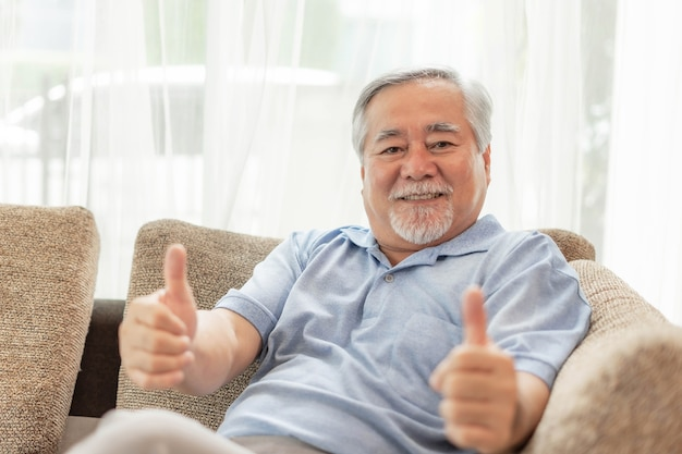 Portrait asian senior man , old man giving a thumb up feel happy good health on couch living room interior background - lifestyle senior male at home concept
