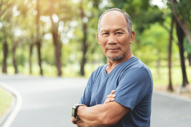 Portrait of asian senior man smiling with arms crossed at park outdoor