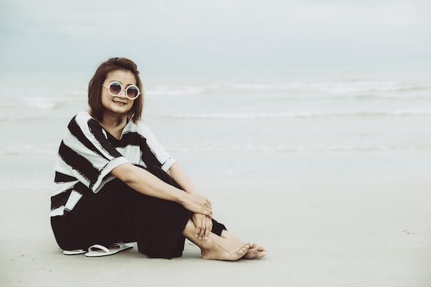 Portrait asian single hipster indy women wear sunglasses lonely siting alone on the beach