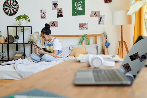 Portrait of asian teenage girl playing ukulele while sitting on bed in cozy room, copy space