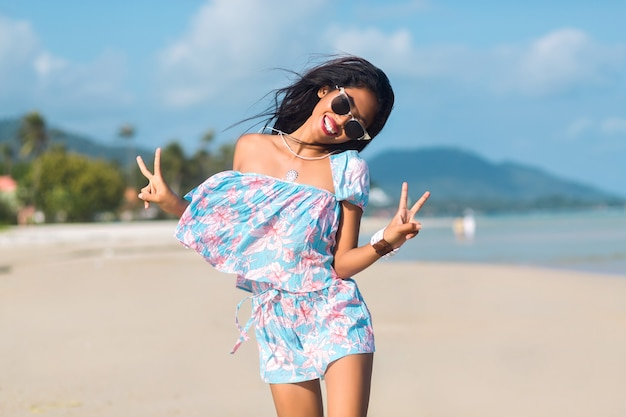 Portrait of asian thai girl with sunglasses and flower dress having fun on tropical beach