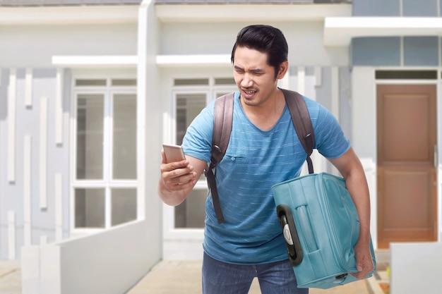 Portrait of asian traveler man running carrying suitcase