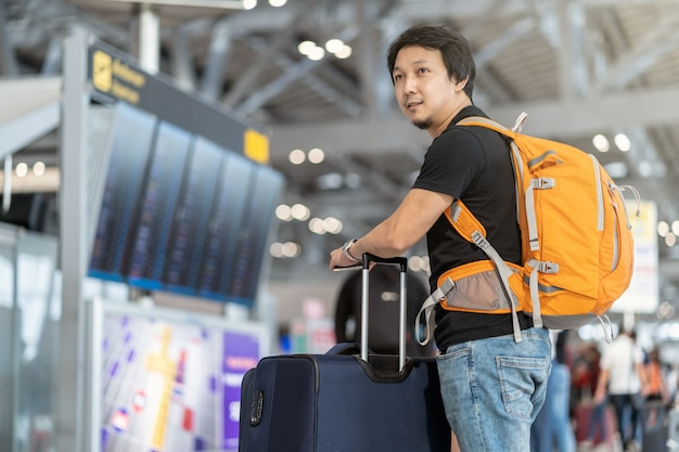 Portrait of asian traveler with luggage with passport standing over the flight board for c