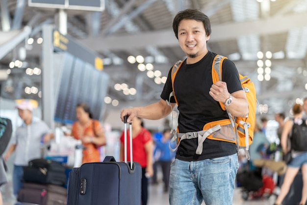 Portrait of asian traveler with luggage with passport standing over the flight board