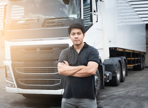 Portrait of asian a truck driver standing cross ones arm with semi trailer truck