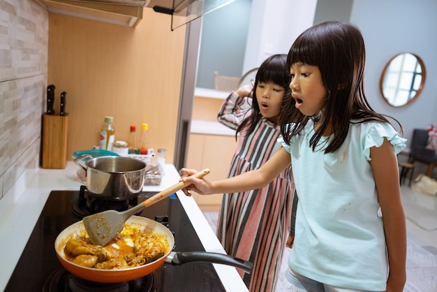 Portrait of asian two little girl cooking in the kitchen
