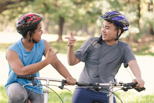 Portrait asian two young man riding bicycle in the park ,man lifestyle concept sport
