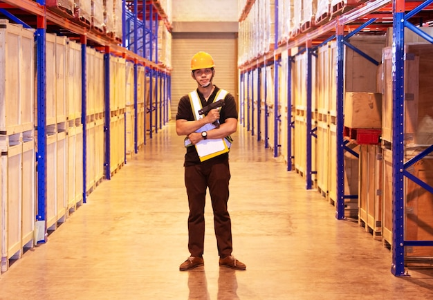 Portrait of asian warehouse worker standing with holding bar code scanner in the storage warehouse