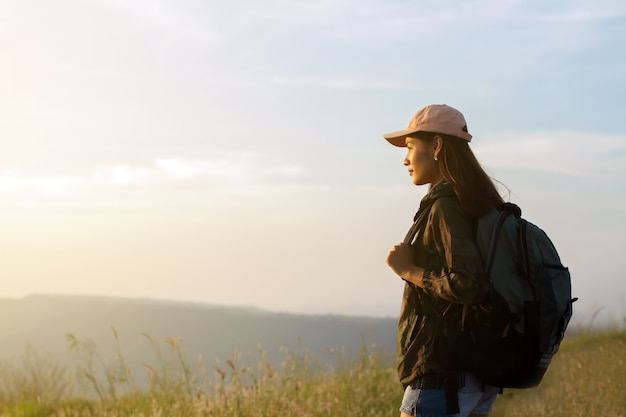 Portrait asian woman backpacking. she was smiling and happy to travel at sunrise seaside mountain pe