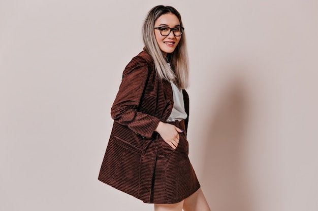 Portrait of asian woman in brown jacket on isolated wall