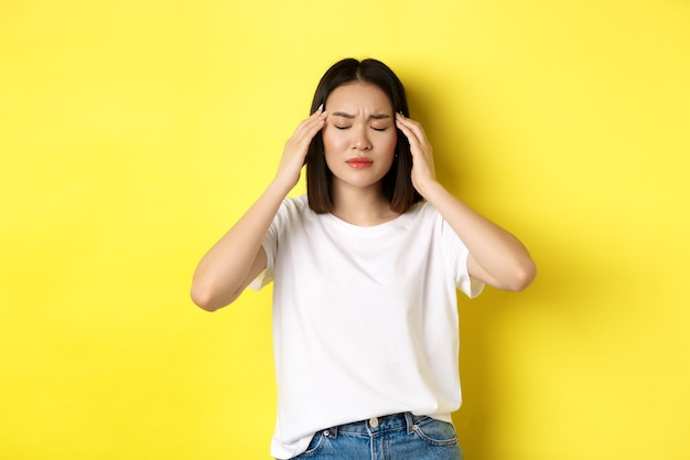 Portrait of asian woman close eyes and frown from migraine, touching head, feeling dizzy from headache, standing over yellow background.