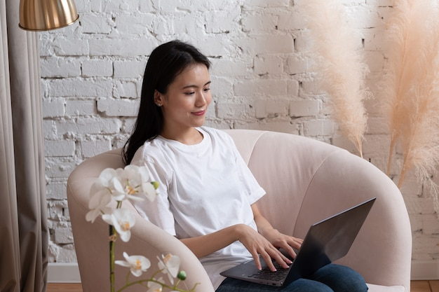 Portrait of asian woman enjoying using laptop at apartment interior indoor living room. video call vlogger webinar stream concept