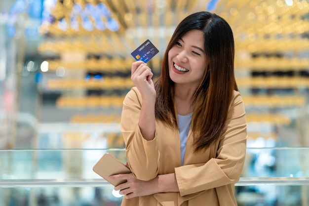 Portrait asian woman holding and presenting the credit card for online shoppin