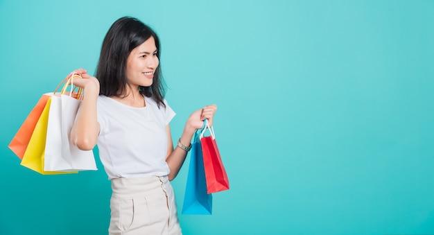 Портрет азиатской женщины, держащей разноцветные сумки для покупок