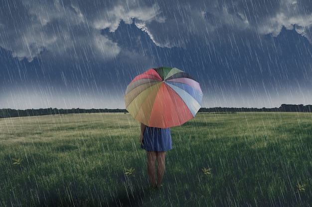 Portrait of asian woman holding umbrella on the green field