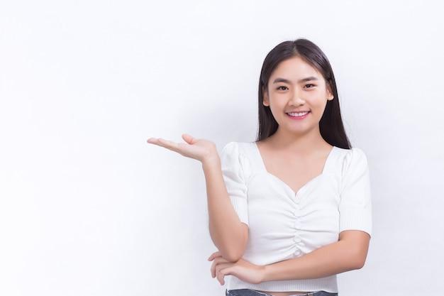 肖像画アジアの女性は笑顔で、白い背景に何かを提示するために彼女の手を示しています。