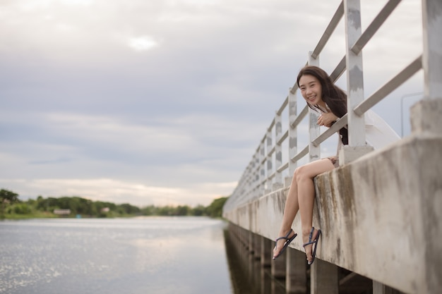 Portrait of asian woman laughing outdoors near the river; happy female smiling over river.