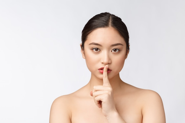 Portrait of asian woman making a hush gesture with finger on lips, isolated