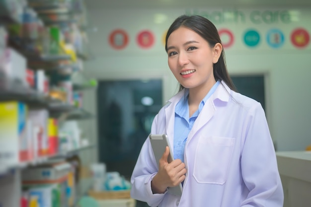 A portrait of asian woman pharmacist using tablet in a modern pharmacy drugstore