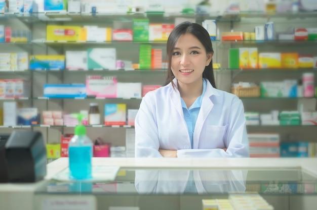 A portrait of asian woman pharmacist wearing lab coat in a modern pharmacy drugstore