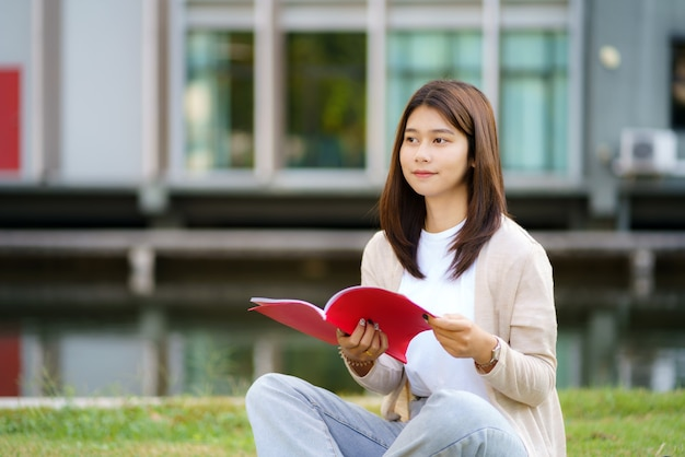 Portrait of asian woman university student aitting on grass in campus looking happy and reading a book in park.