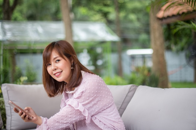 Portrait asian woman using a smart phone in coffee shop garden