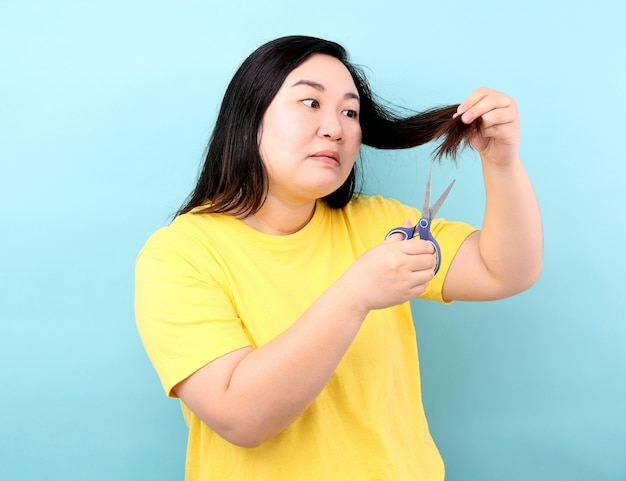 Portrait asian woman wants to cut her damaged hair,on blue background in studio.
