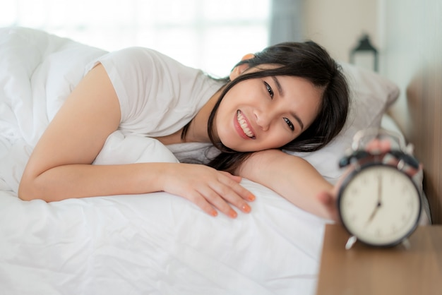 Portrait of asian woman with attractive smile enjoy fresh soft bedding linen mattress with pushing alarm clock at 7 a.m in white bed room modern apartment.