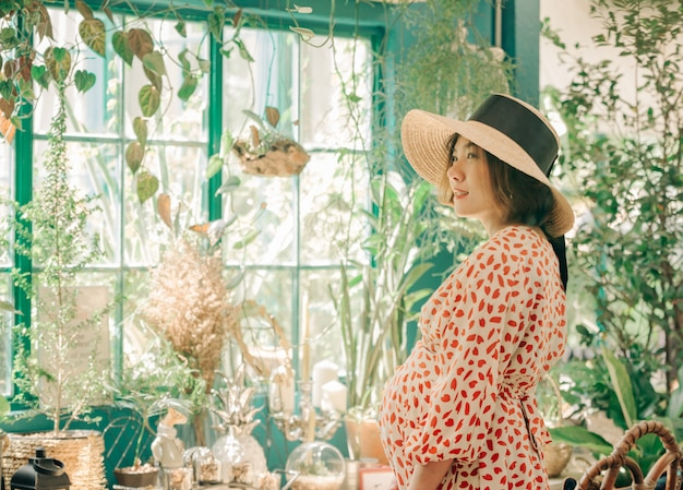 Portrait of asian woman with hat smiling in summer coffee shop cafe vintage color tone.