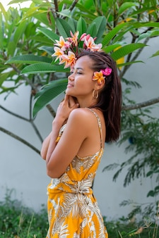 Portrait of asian woman in yellow summer dress stands with plumeria thai flower in hair and round earings female with light make up outside on background of wall and green bushes