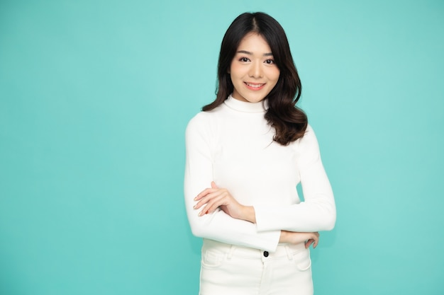 Portrait of asian women with arms crossed and smile isolated over green background