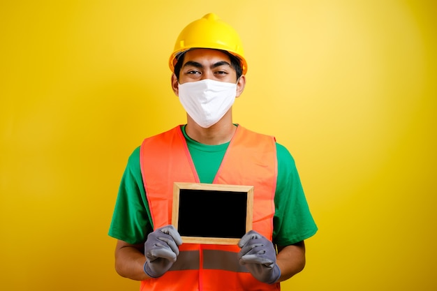 Portrait of asian workman wearing protective mask against the coronavirus, holding small blackboard against yellow background