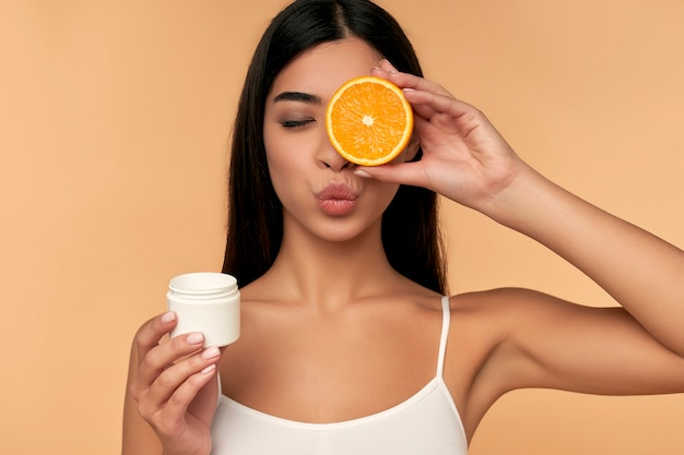Portrait of asian young girl holding orange and moisturizing face cream isolated on beige