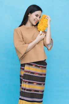Portrait of asian young girl in traditional thai dress and holding  marigold garland