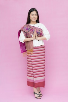 Portrait of asian young girl in traditional thai dress praying isolated on pink background
