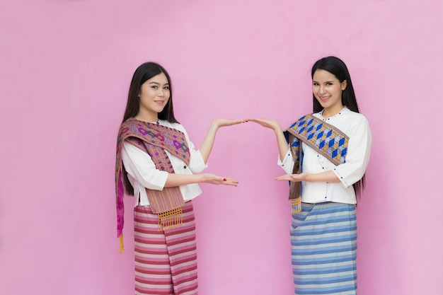 Portrait of asian young girls in traditional thai dress shows blank sign