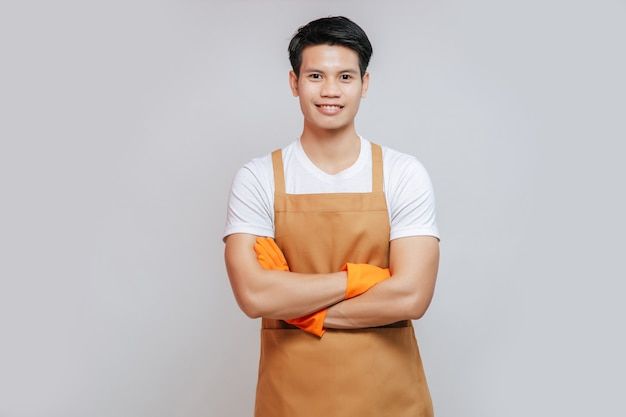 Portrait asian young handsome mand stand with arms crossed,  he wearing apron and rubber gloves, smile and looking to camera, copy space