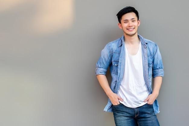 세로 아시아 젊은 남자. 미소 얼굴과 회색 벽 근처에 서있는 잘 생긴 아시아 남자
