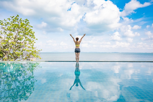 Portrait of asian young woman standing on the pool above the beach feeling so happiness and cheerful,travel in tropical beach in thailand,vacations and relaxation concept