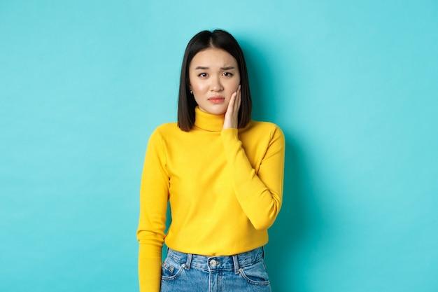 Ritratto di giovane donna asiatica che tocca la guancia e si acciglia, sembra triste, viene schiaffeggiata in faccia, sente mal di denti doloroso, in piedi su sfondo blu
