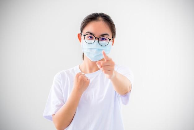 초상화 아시아 젊은 여성은 코로나바이러스로부터 보호하기 위해 마스크를 쓰고, 소녀는 주먹을 들고 손가락을 들고 전염병 개념과 싸우도록 장려합니다.