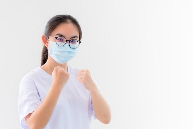 초상화 아시아 젊은 여성은 코로나바이러스로부터 보호하기 위해 마스크를 쓰고, 소녀는 흰색 배경에서 승리하기 위해 바이러스 코비드 19 발병을 막는 전염병 개념과 싸우는 것을 보여주기 위해 주먹을 들고 격려합니다.