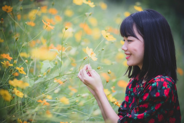 Portrait of asian younger woman model pose in yellow flower blooming field