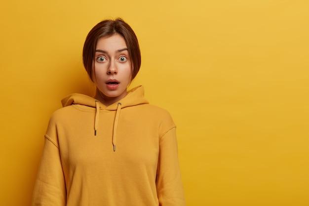 Ritratto di stupito hipster bella femmina trattiene il respiro dall'eccitazione e dalla sorpresa, fissa con gli occhi spalancati, indossa una felpa con cappuccio casual gialla