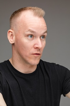 Portrait of astonished blond caucasian man in black talking to someone showing irritation and bewilderment with cropped arms up on grey background.
