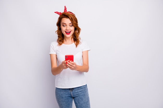 Portrait of astonished crazy girl use smartphone get social network like notification impressed scream wow omg wear stylish clothing isolated over white color wall