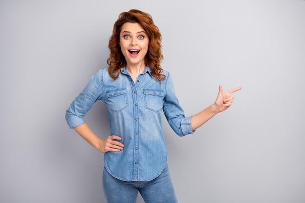 초상화 놀란 정력적 인 여자 발기인 포인트 검지 copyspace 놀라운 광고를 나타냅니다 프로모션 감동 비명 와우 세상에 좋은 옷을 입고 고립 된 회색 벽